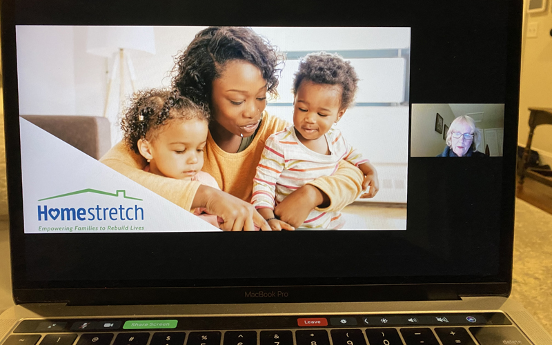 Laptop showing Homestretch presentation with photo of mother with two young children and inset of Nan Monday