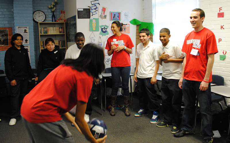 The Grassroot Project volunteers and students playing a game with a ball in a classroom