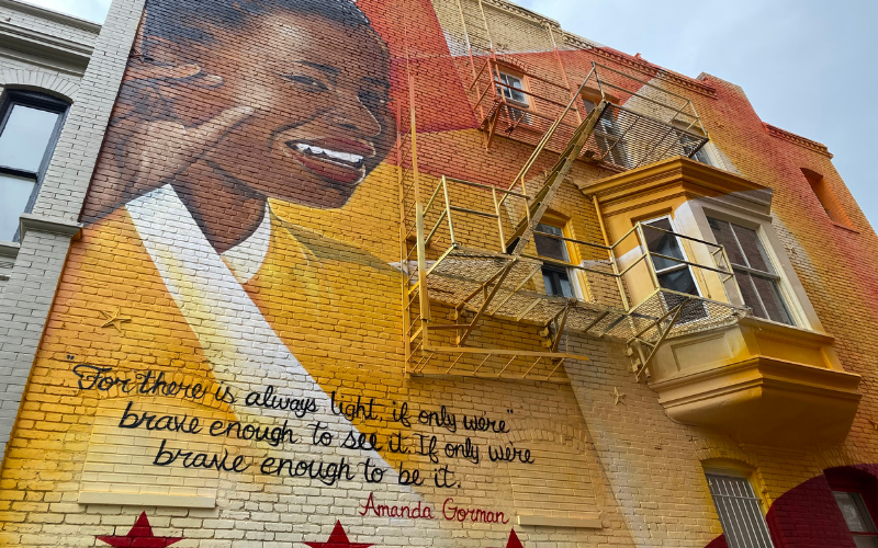 Photo of DC street mural with picture of Amanda Gorman and quote from The Hill We Climb