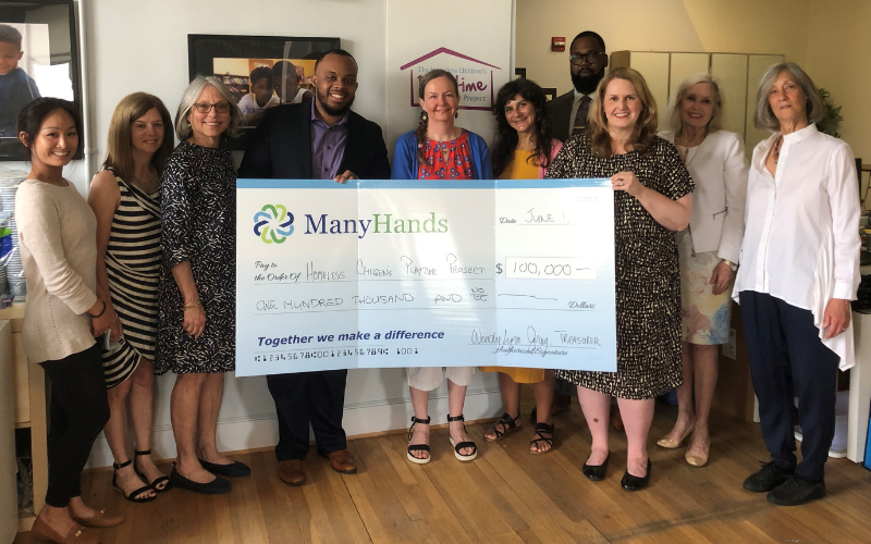 Many Hands members presenting Impact Grant check to Homeless Children's Playtime Project staff