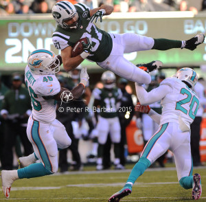 New York Jets tight end Eric Decker is airborne as he is hit by linebacker Neville Hewitt and safety Reshad Jones of the Miami Dolphins Sunday.