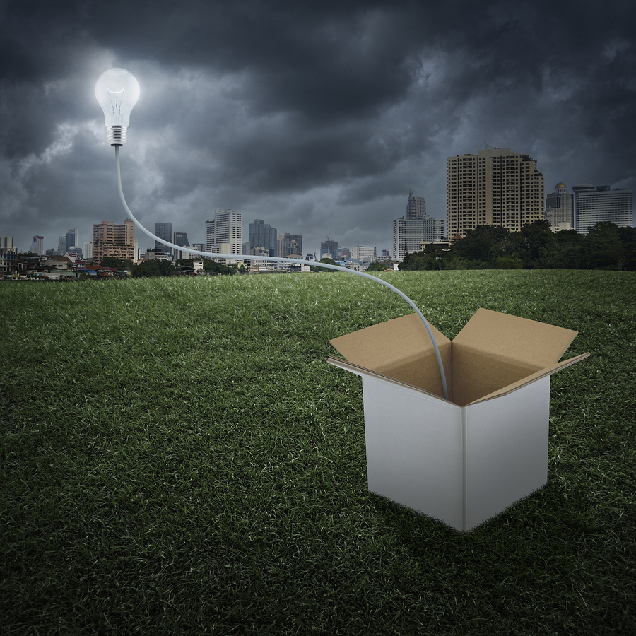 Glowing Light Bulb Float Over Box On City, Think Outside The Box