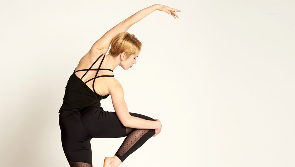 Teen dancer reaches as she holds a beautiful pose.