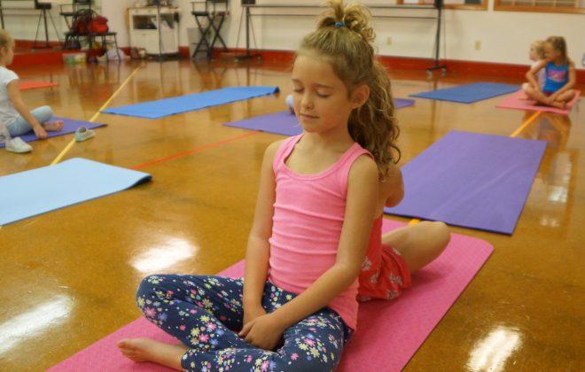Dancers participate in a yoga class.