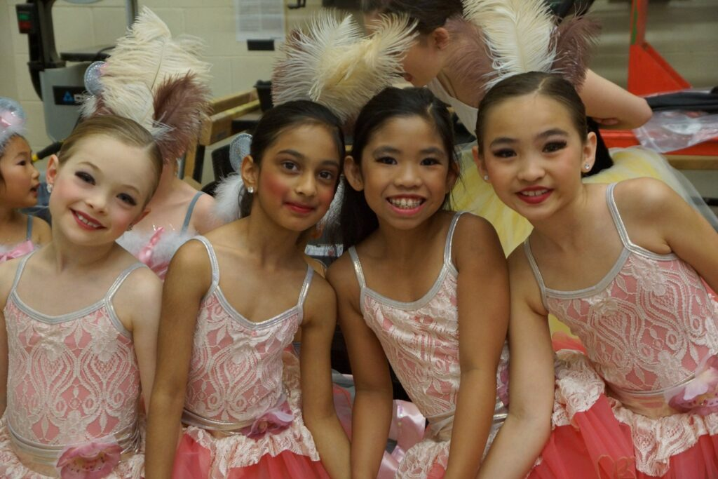 Dancers wearing pink ballet costume with feather in hair