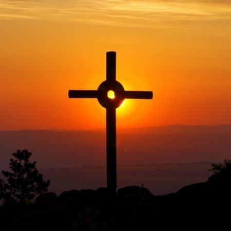 Cross on a hill at sunset