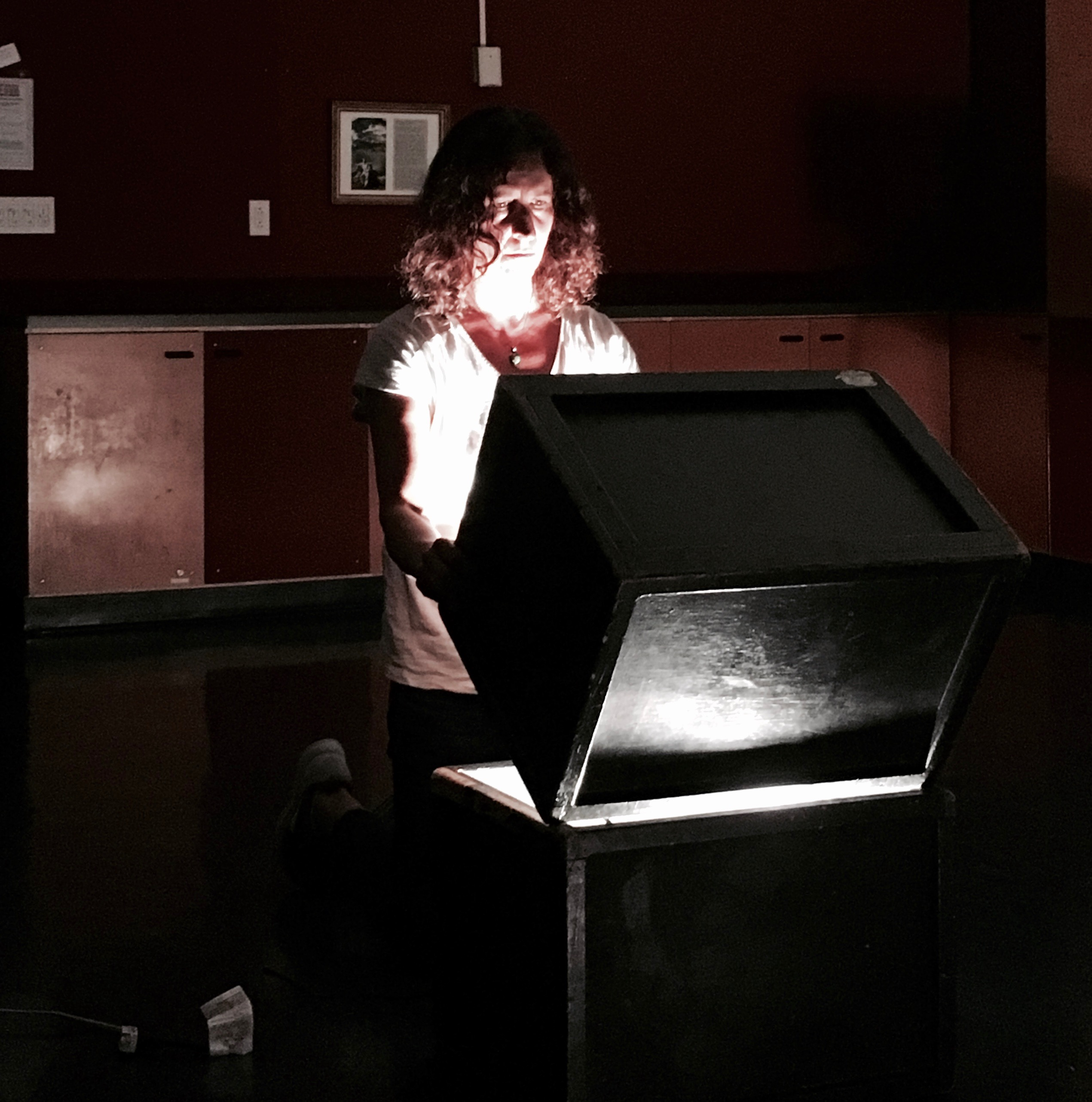 A woman lifts the top half of a box to reveal light within.