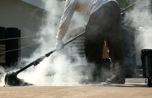 Roofer swinging hot tar mop