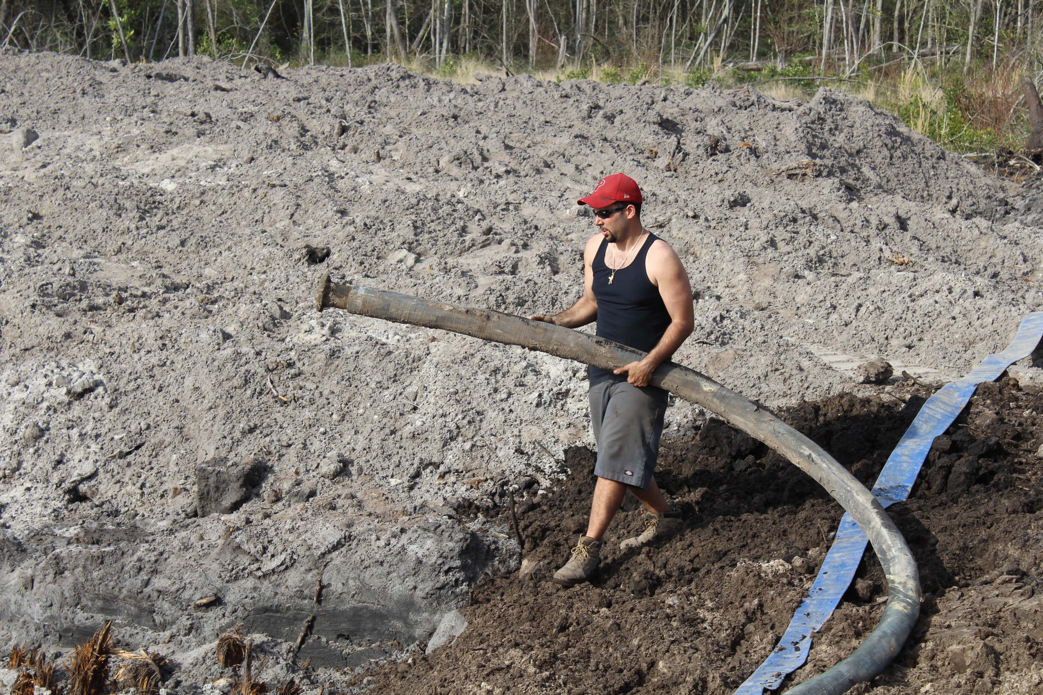 Billy Augustine Jr. places a large water line into a pond