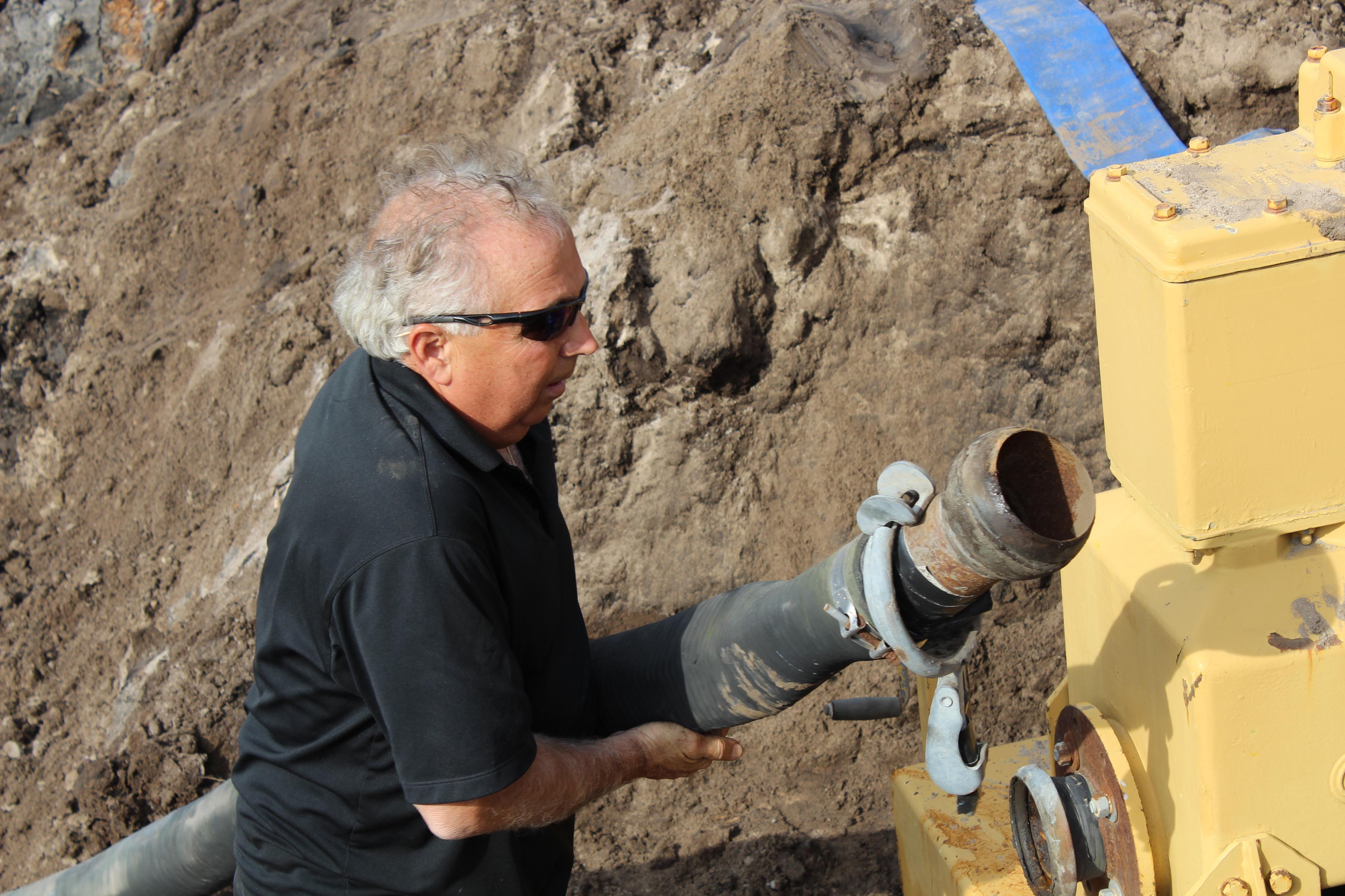 Bill hooks up a large hose to a water pump