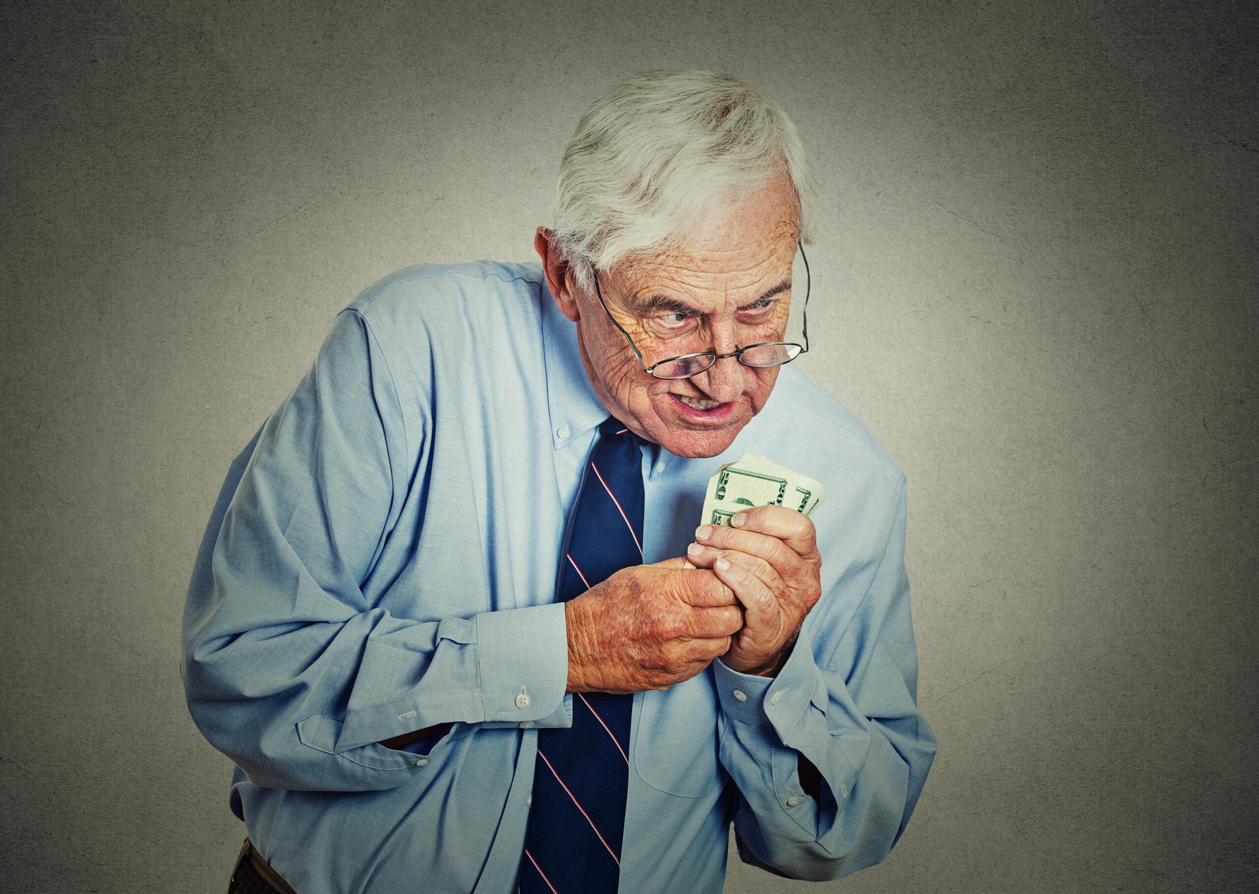 greedy executive, CEO, boss mature man holding dollar banknotes