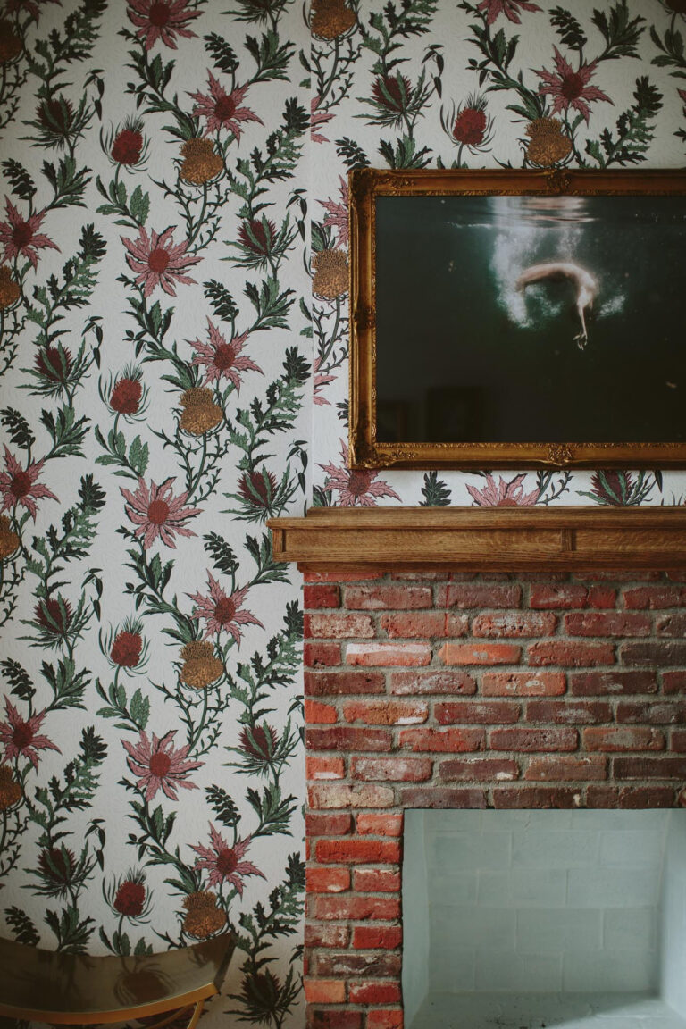 Floral wallpaper over a fireplace