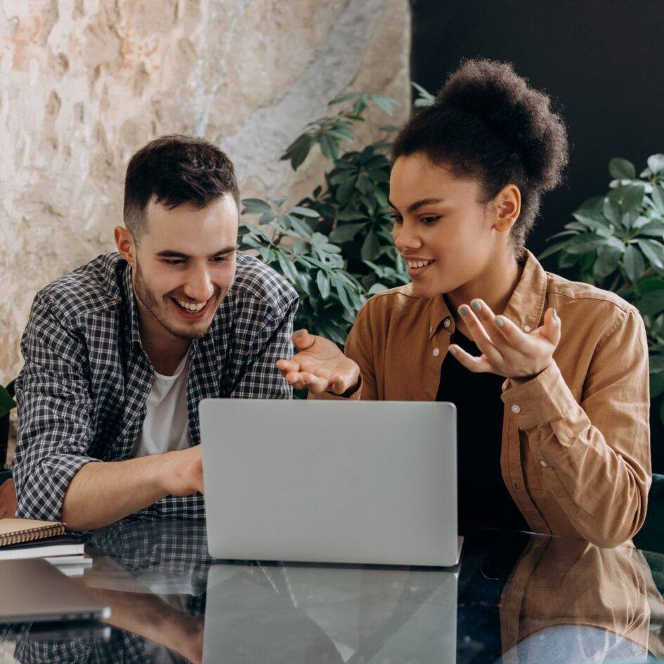 man and woman talking and smiling at each other while working in front of laptop