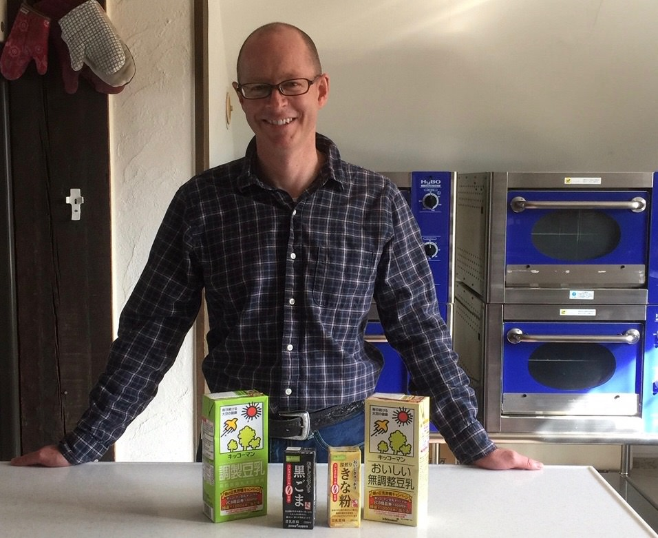 Soy milk vs regular milk and skim milk. Picture of a Brett Standeven standing next to variety of different soy milk on a table.