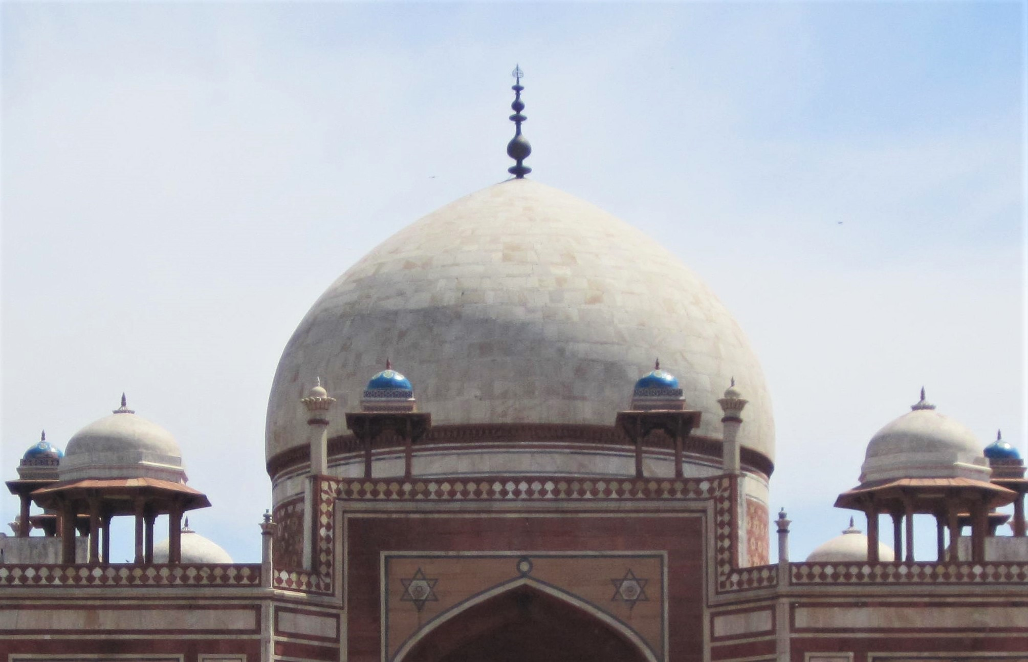The 125ft tall marble-covered central dome with a copper brass finial.