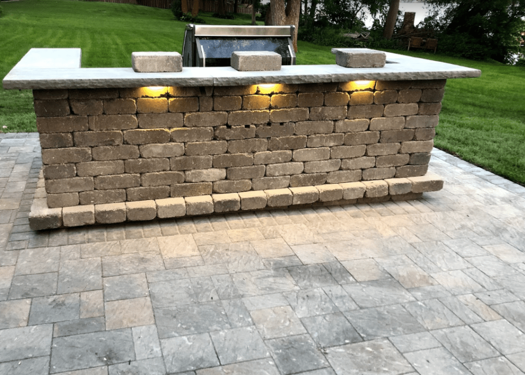 Outdoor kitchen with bar, grill & paver patio