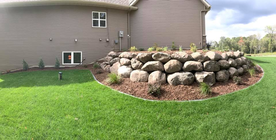 Boulder wall with plantings and mulch
