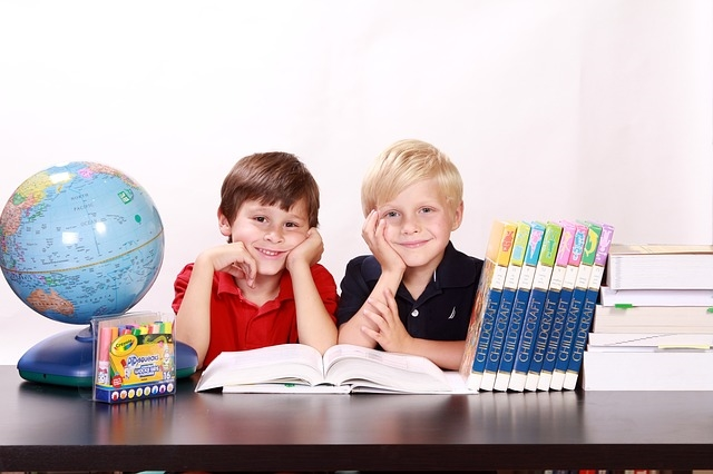 elementary school boys sitting at a desk with a globe and books