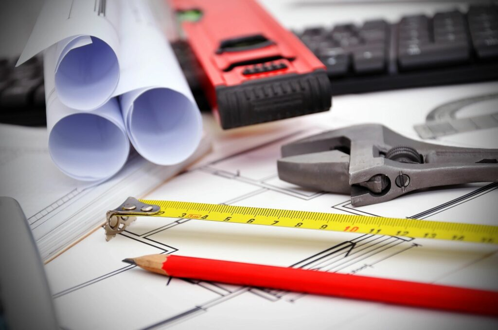 hard hat, tape measure, pencil, wrench, building plans
