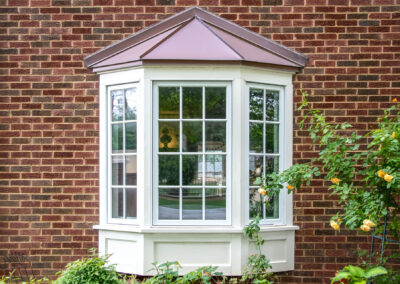 Bay window with copper roof on traditional brick home with flowe