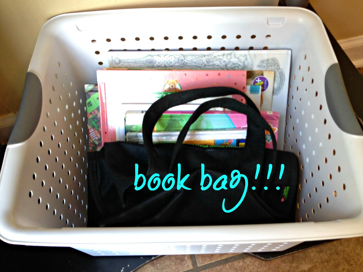 I picked up a little basket at a dollar store and stuffed one of those reusable grocery bags in the front. Now when we need to return books, they're all in one place, with a bag to carry them.