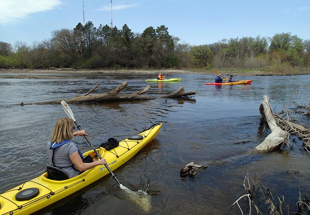 three kayaks heading upstream
