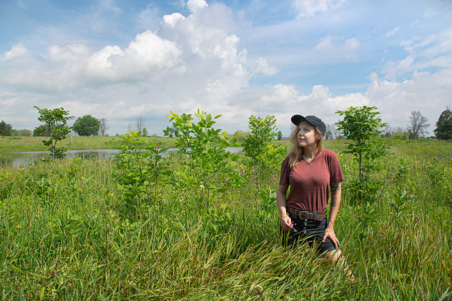 The artist standing in high grass on the prairie at Forest Beach Migratory Preserve with a pond and thunderhead in the background
