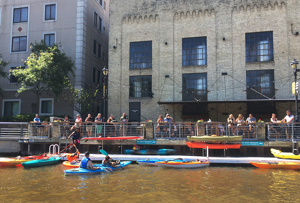 Kayaks docking and people lining the river walk at Lakefront Brewery on the Milwaukee River.