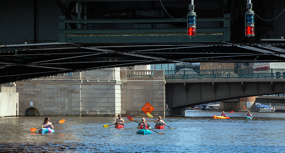 six kayaks appear tiny below the bridges of downtown Milwaukee on the Milwaukee River.