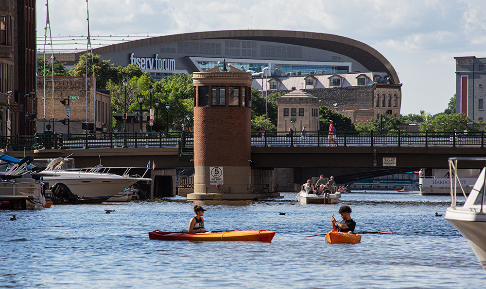 two kayaks and some motorboats on the Milwaukee River in downtown Milwaukee with the Fiserv Forum in the background