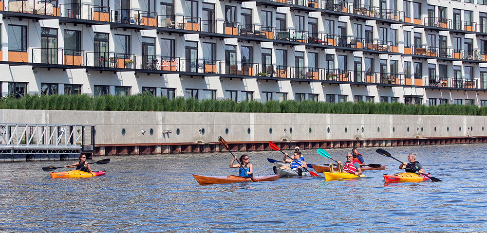 a group of kayaks paddling on the Milwaukee River next to a condo complex