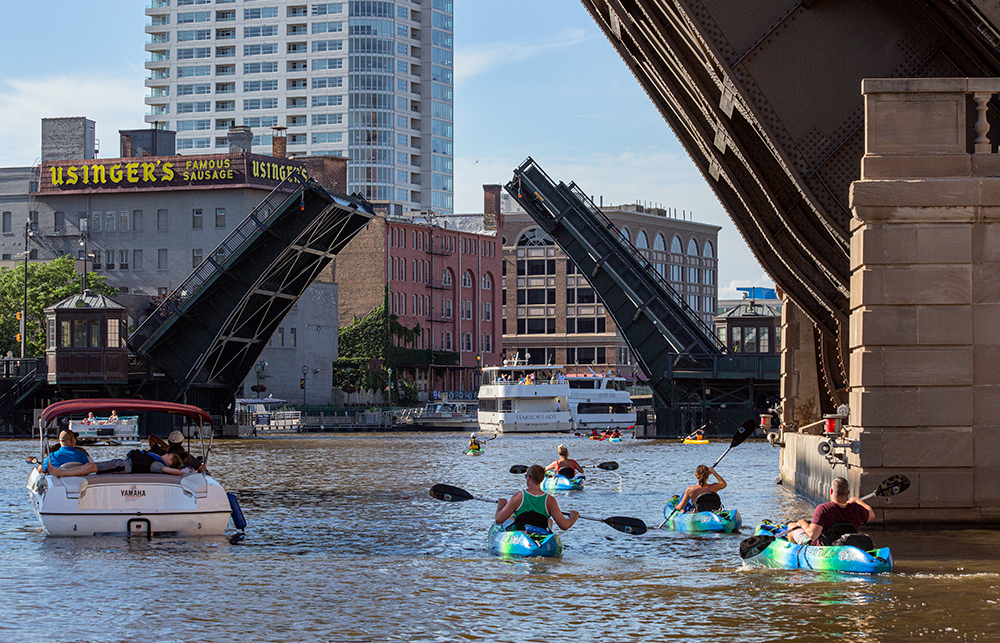 kayaks and a motorboat passing under raised drawbriges in downtown Milwaukee
