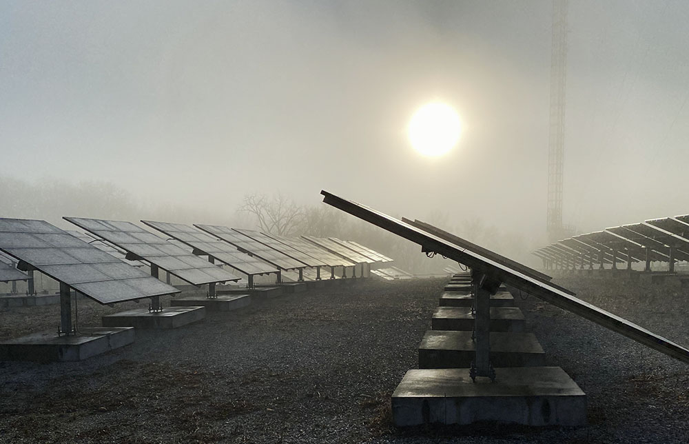 This solar panel array is right next to the Blue Hole, seen as the sunrise burns through the fog.