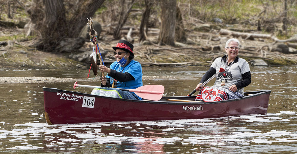 Native Americans in canoe on Milwaukee River