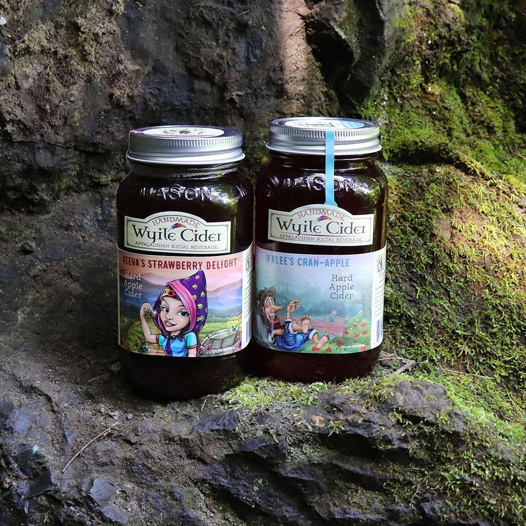 2 mason jars with Wyile Cider on a tree stump