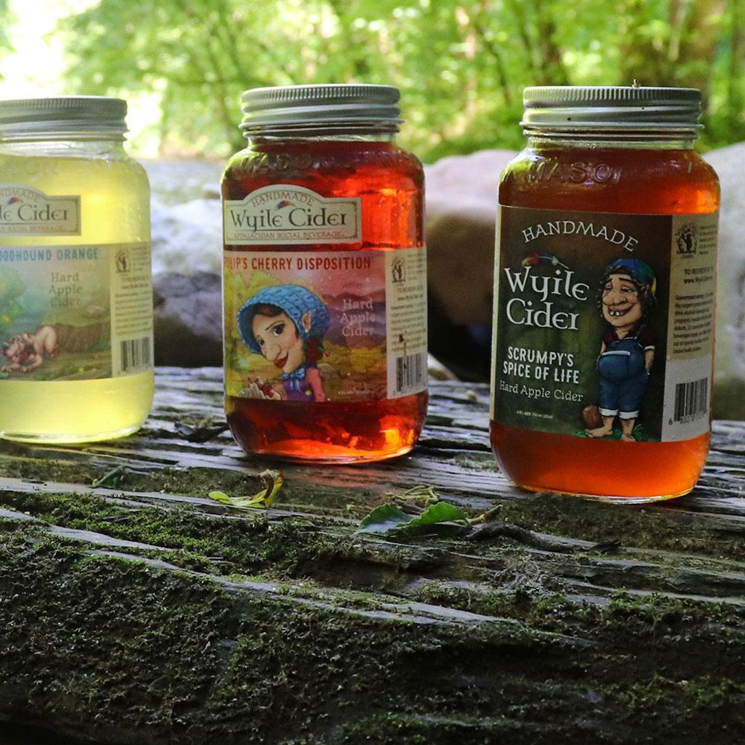 3 mason jars with Wyile Cider on a log