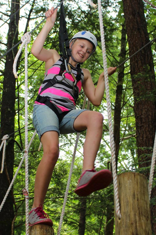 Girl walking the arial circuit at Foxfire Mountain adventure park