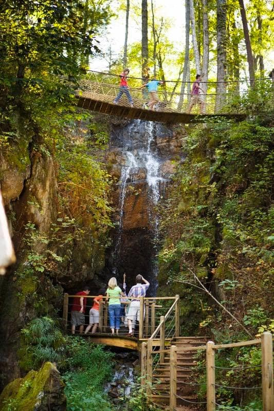 photo of people walking on bridges above and below the falls at Foxfire Mountain