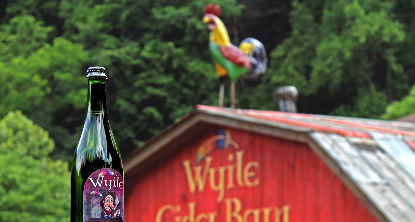 bottle of sparking Wyile Cider in the foreground in front of the Wyile Cider Barn