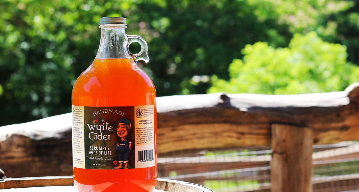 "Jug of Wyile Cider ""Spice of Life"" Cider with forest background"