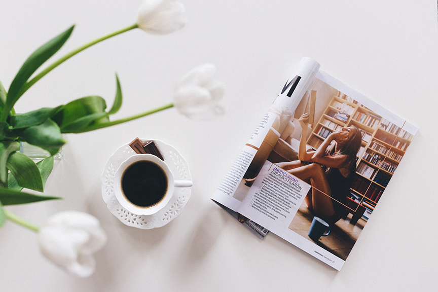 Digitally printed magazine and coffee cup on table.