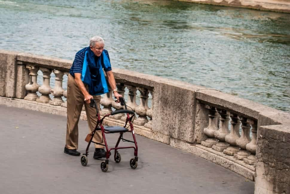 old big and tall man using a walker by the water
