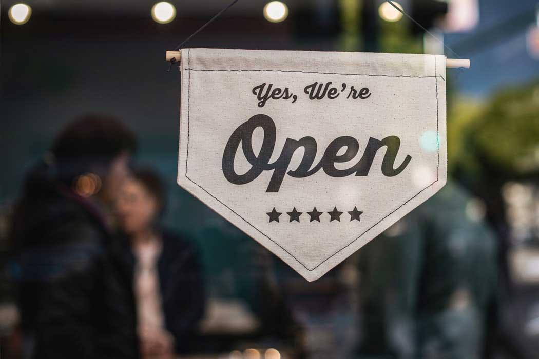 A door sign declaring a business open.