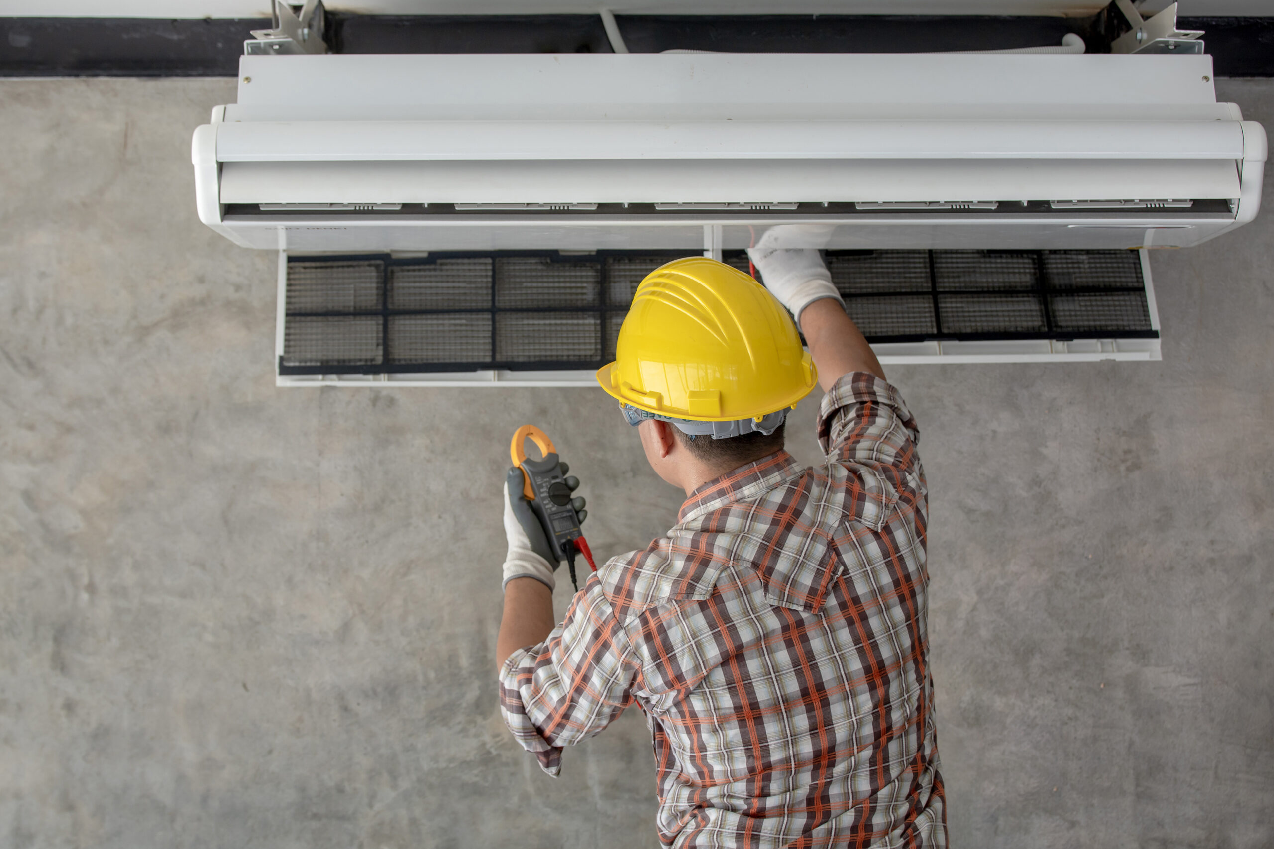 A technician in process of inspecting and maintaining an hvac ductless system.