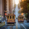 Classic view of historic traditional Cable Cars riding on famous California Street in beautiful early morning light at sunrise in summer, San Francisco, California, USA