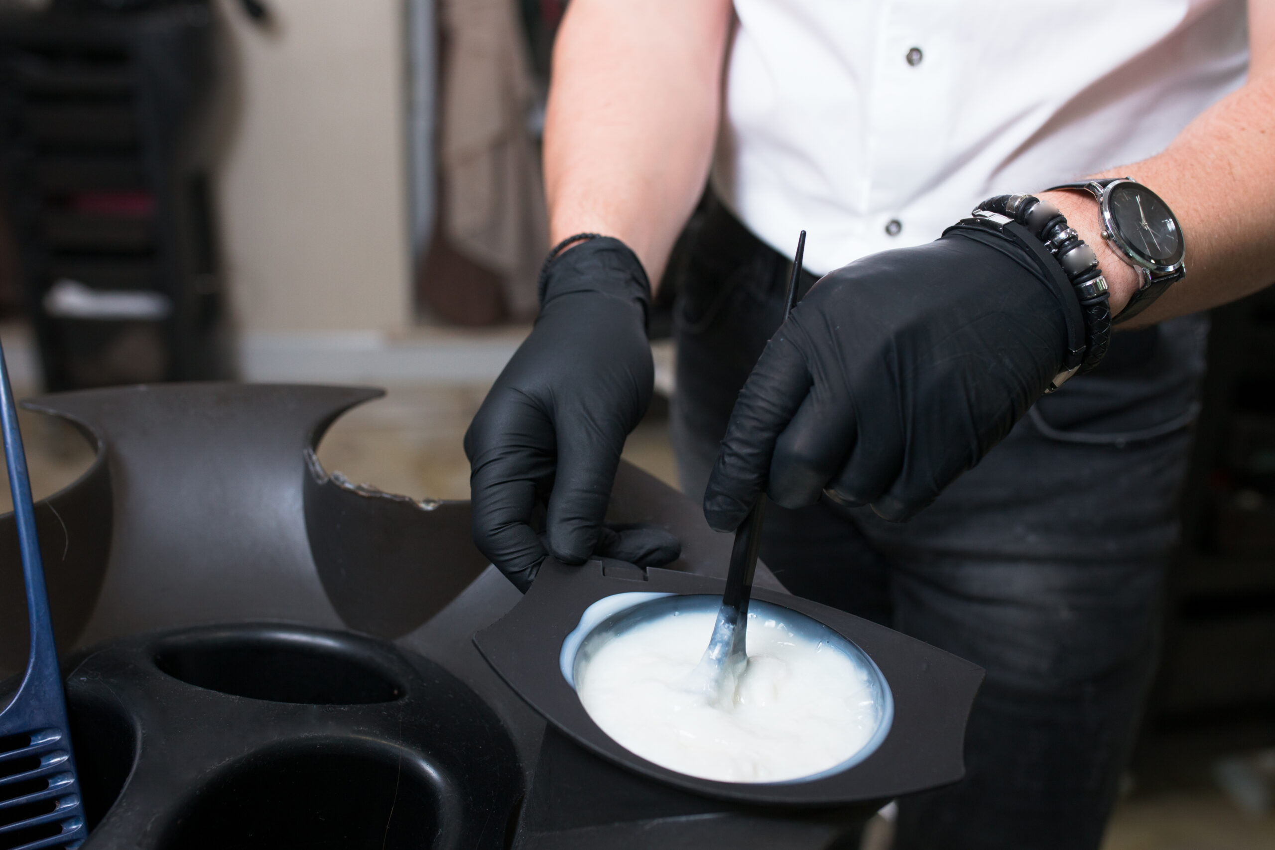 Male Stylist in gloves preparing color cream for dying hairin  a container, a mask for treatment procedure in beauty salon. Hhairdresser mixing brush coloring hair concept supplies. Spa copy space
