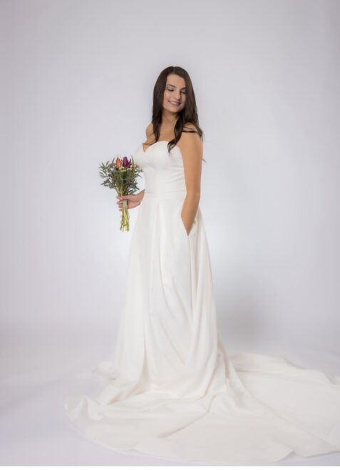 Strapless wedding dress with pockets and long train from bridal boutique in west bend Wisconsin
