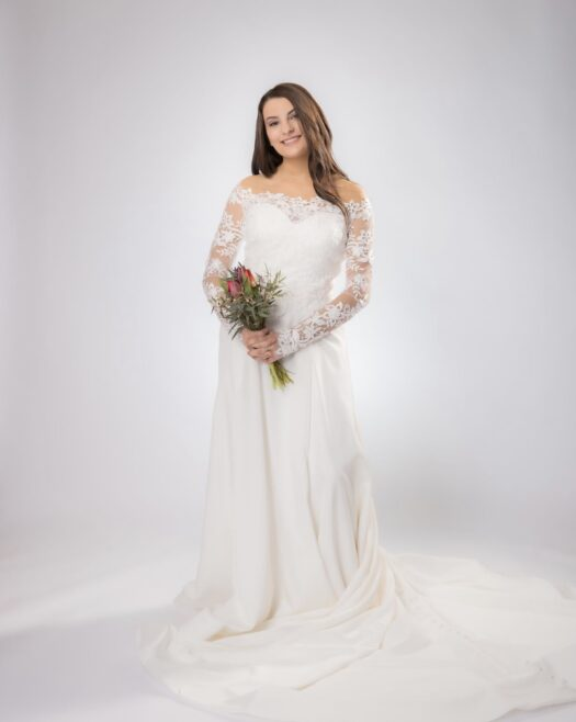 Wedding dress with clean lines and removable lace jacket at bridal shop in west bend Wisconsin