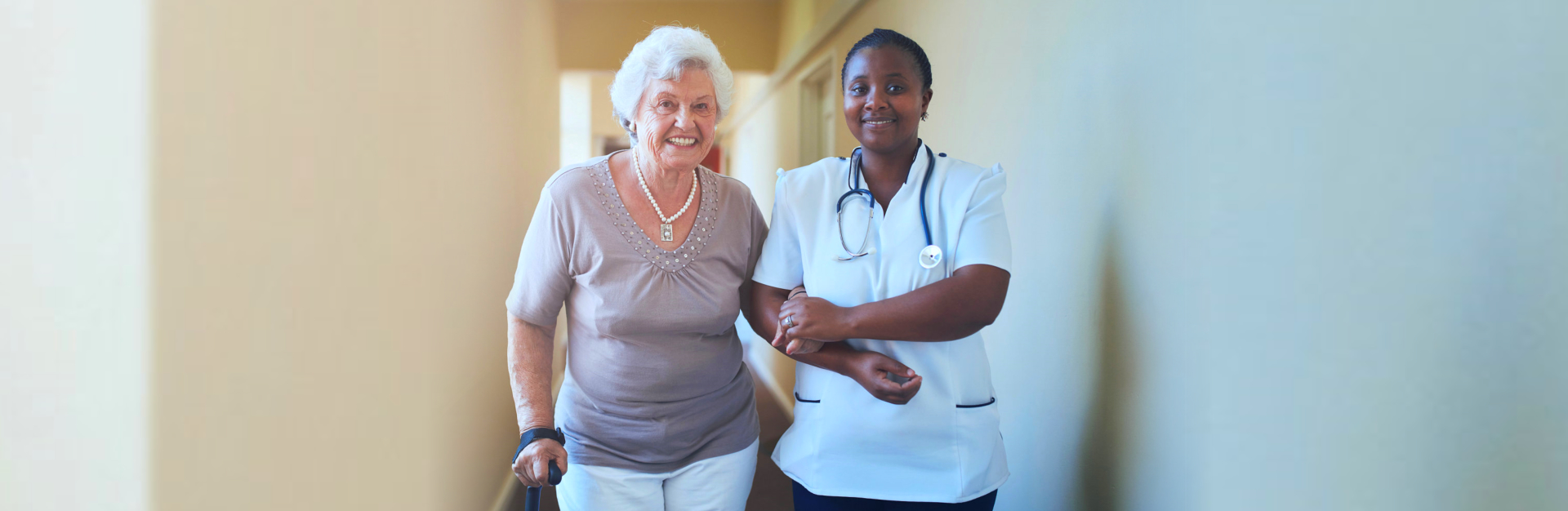 senior woman with caregiver walking in the hallway