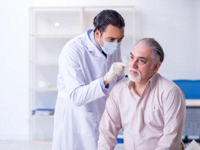 doctor checking elder man's ears